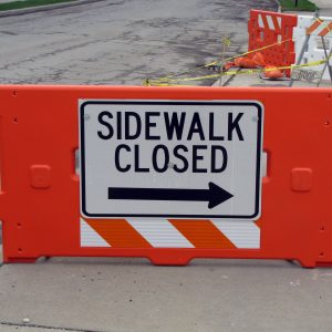 """Orange Barricade With A Sign That Says """"Sidewalk Closed"""" Attached"""