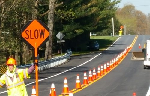 """Flagger In Yellow Reflective Gear Holding A Sign That Says """"Slow"""" To Direct Traffic Through A One-Way Lane"""