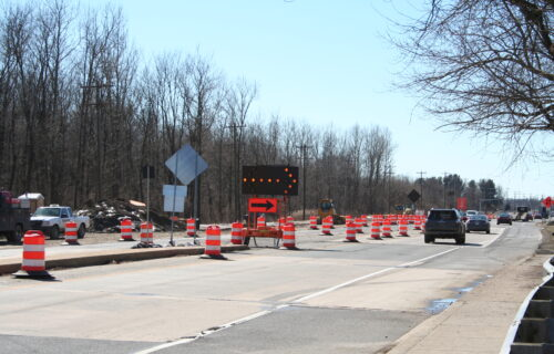 Maintenance of Traffic road closure with flashing arrow board and orange and white traffic barrels