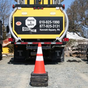 Stack Of Orange And White Traffic Cones In Front Of Yellow Traffic & Safety Signs Truck
